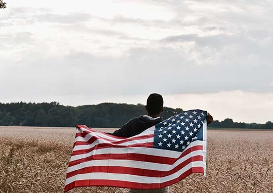 Student runs through the field with American Flag